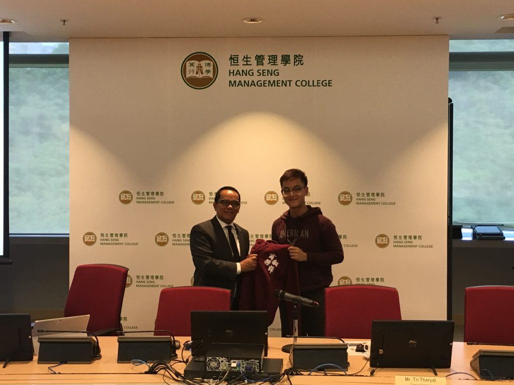 Mr. Tharyat receives a hoodie from a representative of the Students Association of Translation with Business